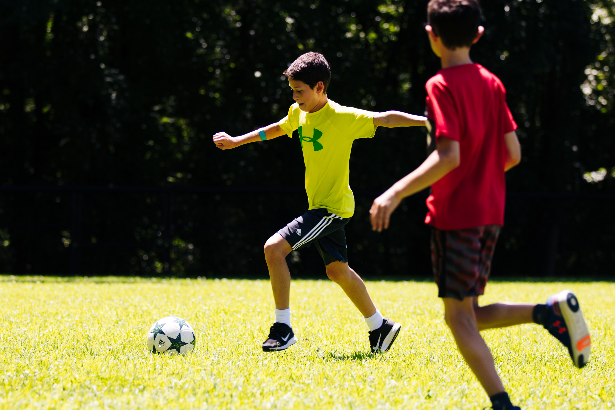 Two campers playing soccer outside