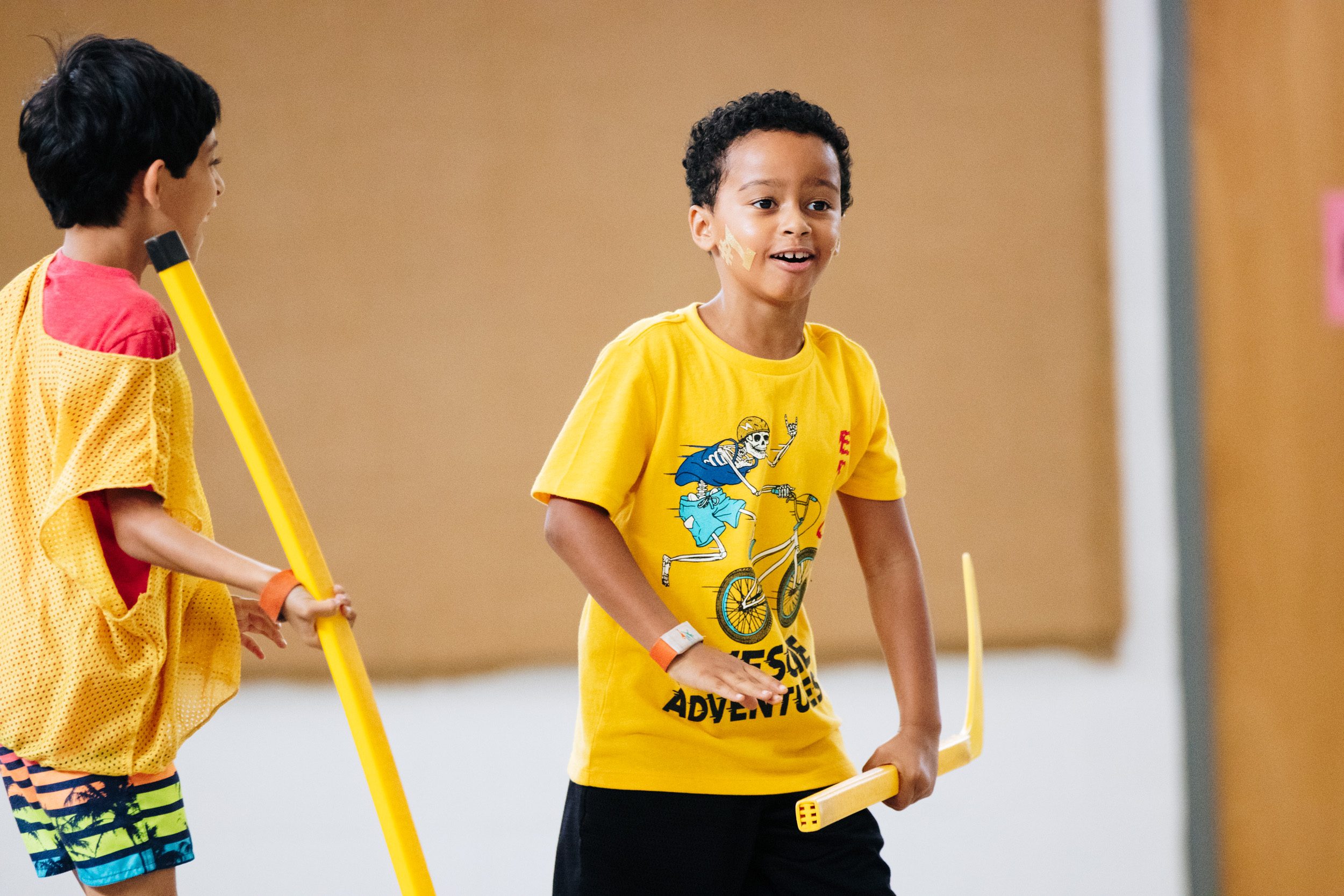 Two boys on the yellow team playing indoor floor hockey