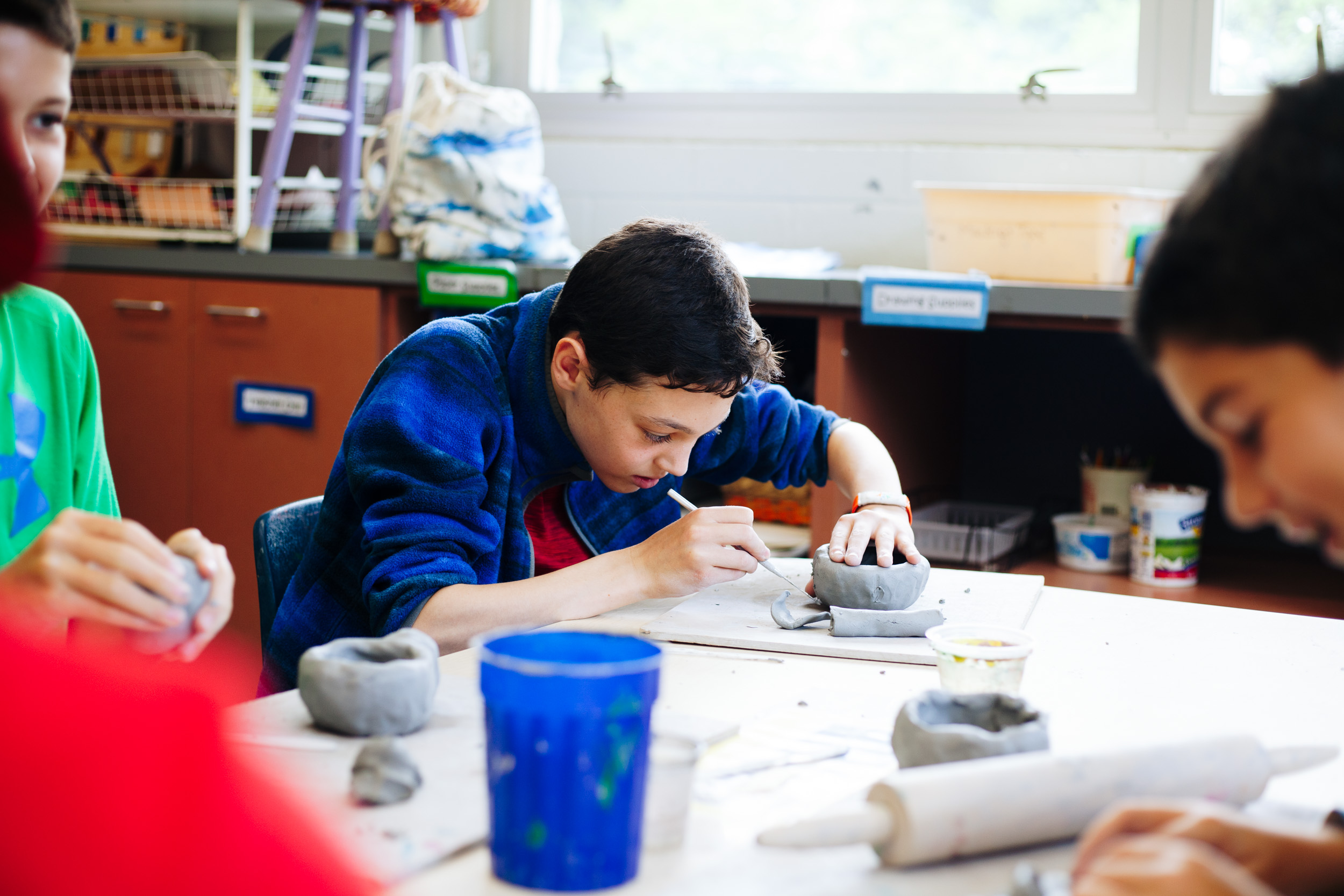 Campers making ceramic bowls with clay